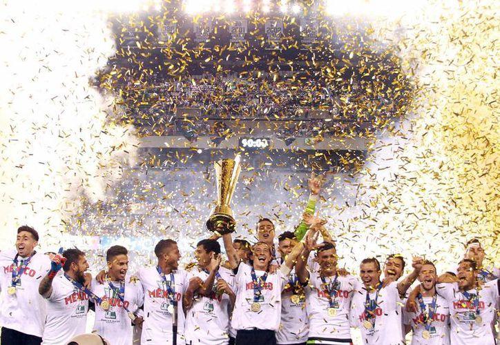El duelo decisivo entre México y Estados Unidos cambia de fecha, se disputará el 10 de octubre, en la imagen, jugadores del 'Tri' con la Copa Oro que ganaron ante Jamaica. (Archivo/Notimex)