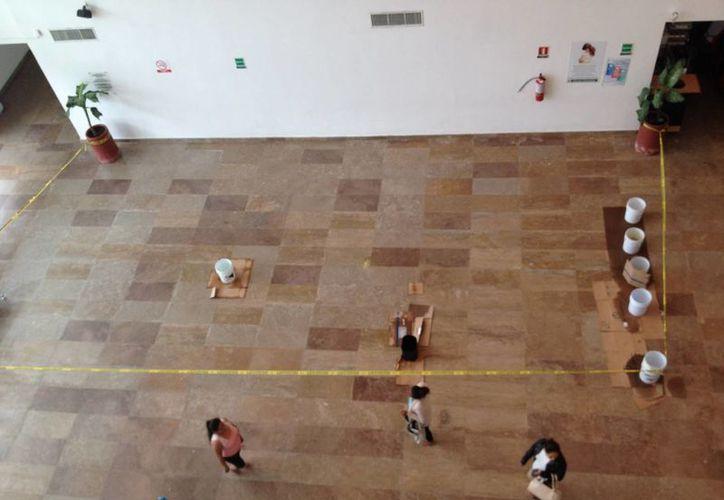 Para contener el agua que cae del techo, trabajadores del hospital colocan cubetas. (Adrián Barreto/SIPSE)