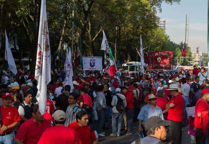 Contingentes de trabajadores empezaron a reunirse en Paseo de la Reforma, para marchar rumbo al Zócalo capitalino para conmemorar el Día del Trabajo. (Notimex)