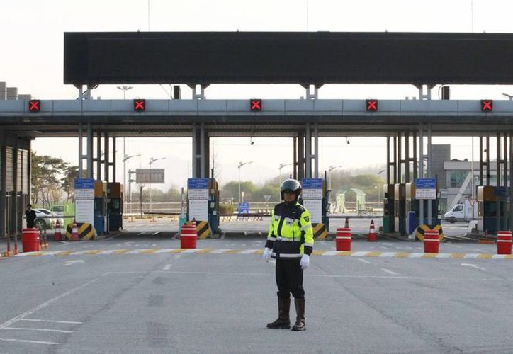Un policía surcoreano frente a la oficina de aduana, inmigración y cuarentena cerca de la aldea fronteriza de Panmunjom, que separa ambas Coreas, en Paju, Corea del Sur. (Agencias)