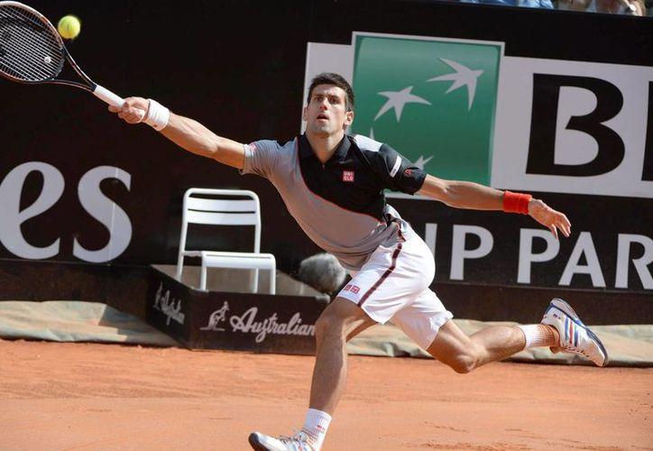 El tenista serbio Novak Djokovic devuelve la bola al canadiense Milos Raonic, durante la semifinal del Torneo de Roma que se disputa en el Foro Italico. (EFE)