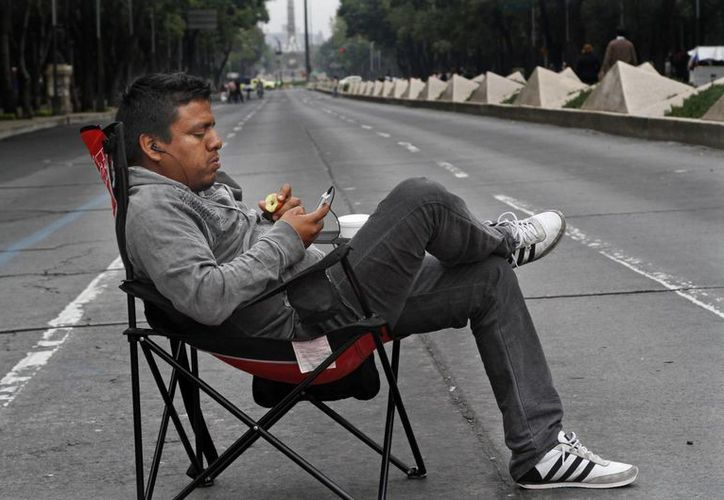 Un maestro revisa su celular en Paseo de la Reforma, el martes. La CNTE continuó con sus movilizaciones en la Ciudad de México dejando graves afectaciones. (Agencias)