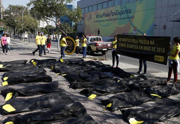 """Activistas de Amnistia Internacional (AI) protestan con una pancarta en donde se lee """"40 muertos por la Policía en la ciudad olímpica en mayo de 2016"""" y con bolsas para cadáveres frente a las sede del Comité Olímpico local en Río de Janeiro. (EFE)"""