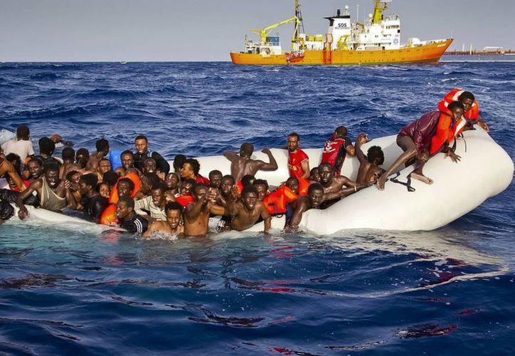Migrantes piden la ayuda de un barco del bote a medida que se acercaban por el auxilio de un barco, al fondo, frente a la costa de la isla italiana de Lampedusa.  (Patrick Bar / SOS Mediterranee a través de AP)