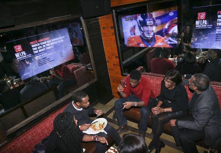 La edición del Super Bowl  28 rompió todos los récord de audiencia en televisión. En la imagen, aficionado miran el juego en pantallas, en un bar. (Agencias)