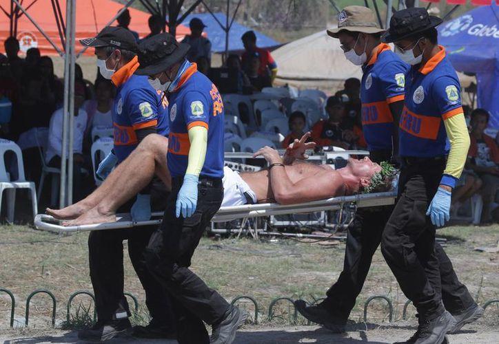 El cineasta danés Lasse Spang Olsen es conducido al hospital tras crucificarse en Filipinas. (AP)