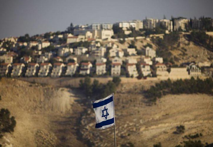 Una bandera israelí se ve frente al asentamiento judío cisjordano de Maale Adumim, en las afueras de Jerusalén. (Agencias)