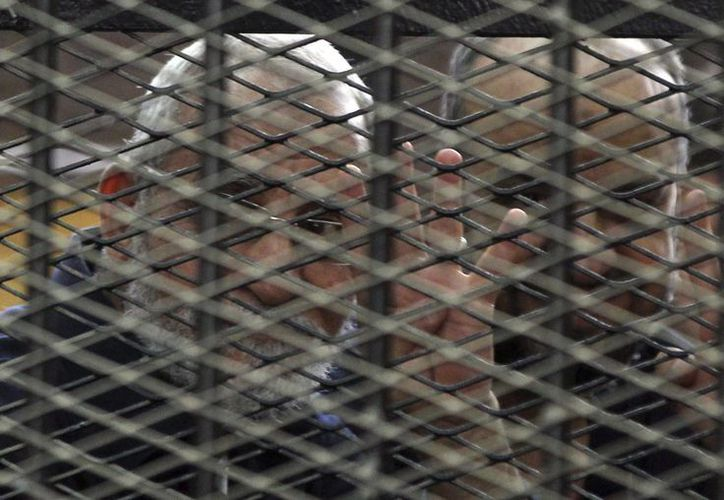 Mohamed Badie hace la señal de los cuatro dedos desde detrás de unas rejas, durante un juicio en El Cairo, Egipto. (EFE)