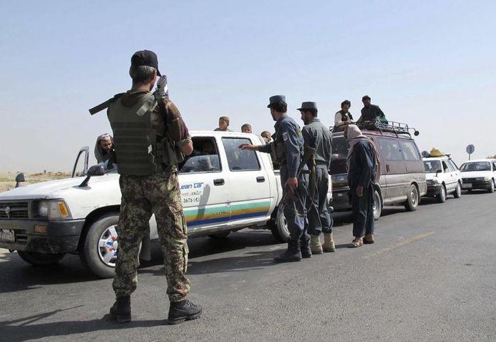 Oficiales de seguridad afganos inspeccionan vehículos a su llegada a Lashkar Gah, en Afganistán. (EFE/Foto de contexto)
