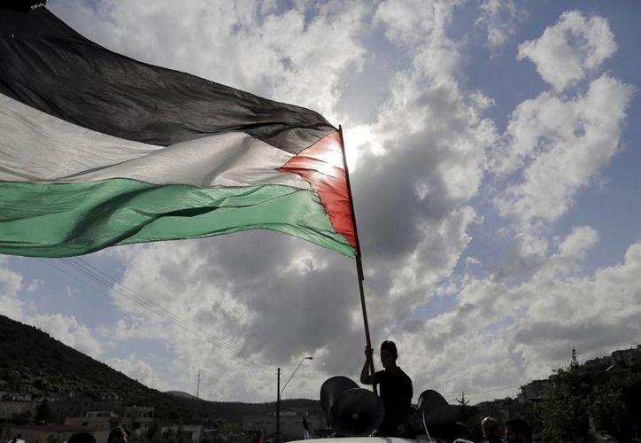 La prolongada disputa por territorio entre Palestina e Israel parece no tener final. En la imagen, un hombre enarbola una bandera palestina en una manifestación antiisraelí. (ibtimes.co.uk)