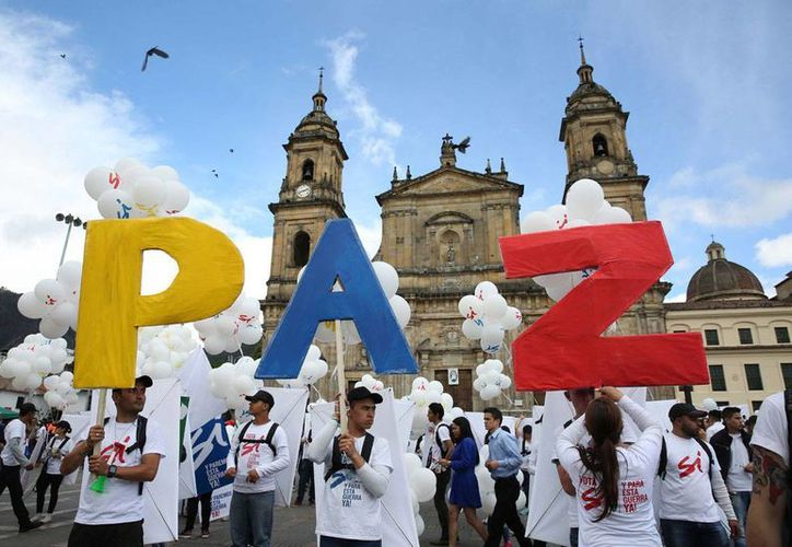 Varios jóvenes se manifiestan en la Plaza Bolívar de Bogotá, Colombia, tras la firma del acuerdo de paz entre el Gobierno y las FARC, en Cartagena de Indias, el lunes 26 de septiembre de 2016. (Foto: AP/Jennifer Alarcon)