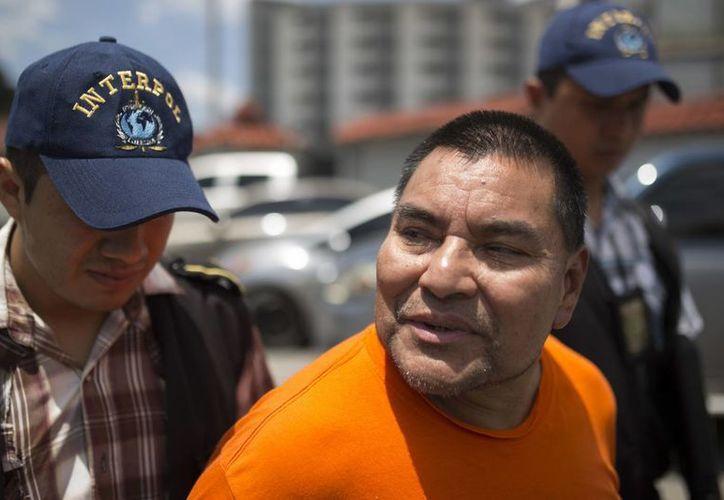 El ex soldado Santos López Alonzo es escoltado por agentes de la Interpol luego de aterrizar en la base de la Fuerza Aérea en Ciudad de Guatemala el miércoles 10 de agosto de 2016. (AP Foto/Luis Soto)
