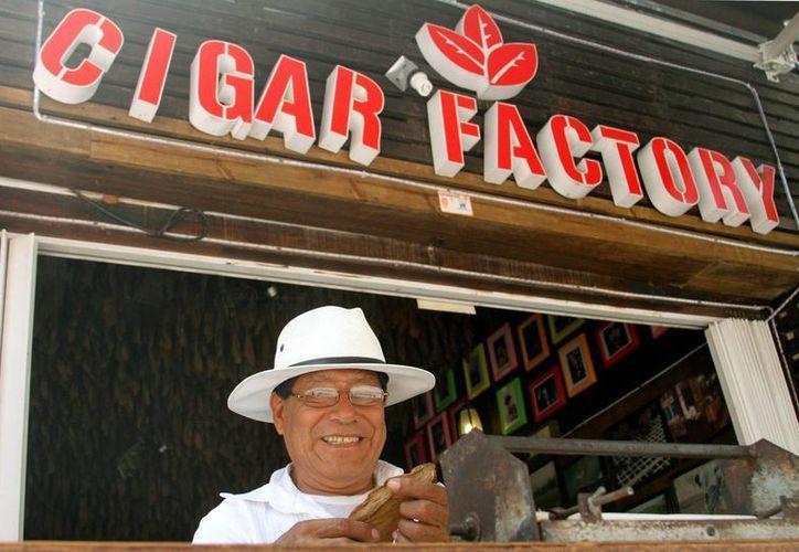 Cándido Cagal desde hace ocho años se sienta  de 9 am a 11 pm en la Quinta Avenida a enrollar en promedio 200 puros al día.  (Adrián Monroy/SIPSE)