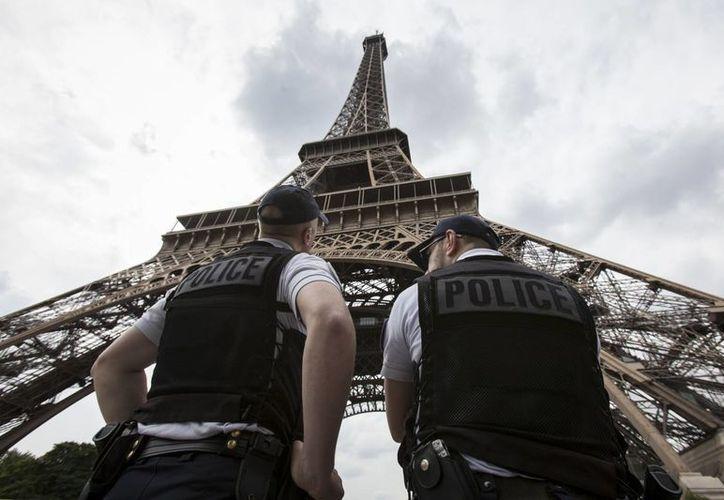 Imagen del 10 de junio de 2016, que muestra a oficiales de policía vigilando en el exterior de la Torre Eiffel, en París, Francia. La icónica torre será blindada para evitar ataques terroristas. (AP/Kamil Zihnioglu)