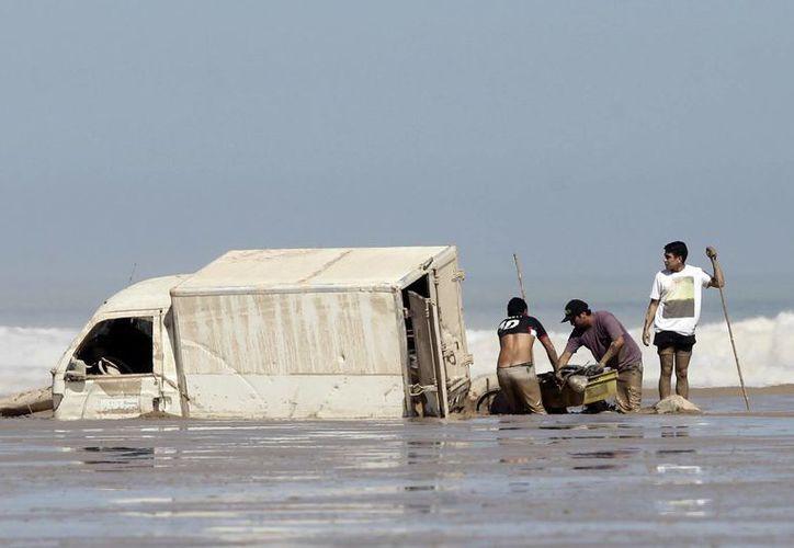 Dos hombres descargan mercancía de un vehículo varado en la playa de Charañal tras los efectos del caudal del río formado por inundaciones torrenciales en Chile. (EFE)