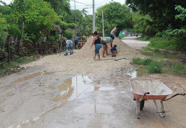 Habitantes de la colonia Benito Juárez de Bacalar se organizaron para tapar los baches de sus calles. (Javier Ortiz/SIPSE)