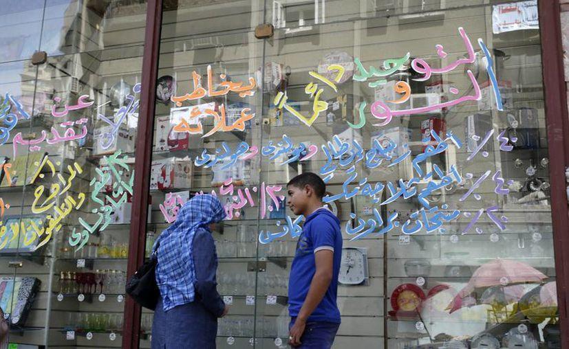 Una mujer egipcia busca artículos con descuento para la venta en la tienda de Tawhid y Nour, en El Cairo. (Agencias)