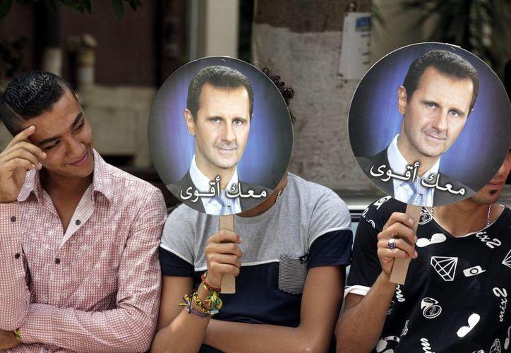 Ciudadanos sirios residentes en Egipto muestran retratos del actual presidente, Bachar Al Asad, para manifestar su apoyo para los comicios presidenciales en Siria, delante de la embajada siria, en El Cairo. (EFE/Archivo)