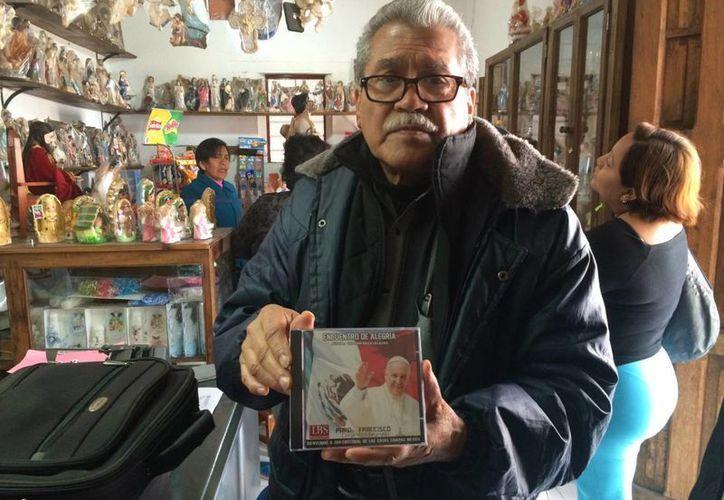 Lehabin Baza Salazar posa con el disco en donde están las canciones que hizo para el Papa Francisco. (Luis Soto/SIPSE)