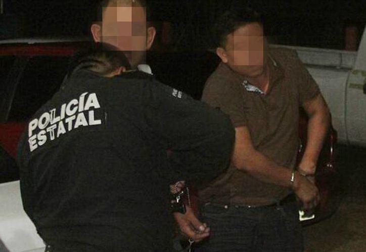 Dos de los detenidos, al ser momento de ser esposados por un agente de la SSP en el retén entre Dzilam Bravo y Dzilam González. (Milenio Novedades)