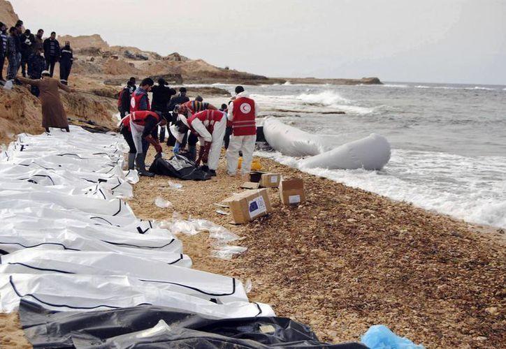 Imagen de este lunes en donde muestra a elementos de la Federación Internacional de Sociedades de la Cruz Roja y de la Media Luna Roja (FICR) mientras rescatan y acomodan los cuerpos de decenas de inmigrantes cerca de Zawiya, Libia. Al parecer, las víctimas eran africanos que desembarcaron al oeste de ese país y viajaban rumbo a Europa. (Mohannad Karima / IFRC vía AP)