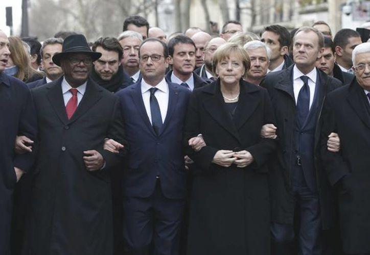 Francois Hollande del brazo con Angela Merkel y demás líderes que lo acompañaron en la jornada. (Agencias)