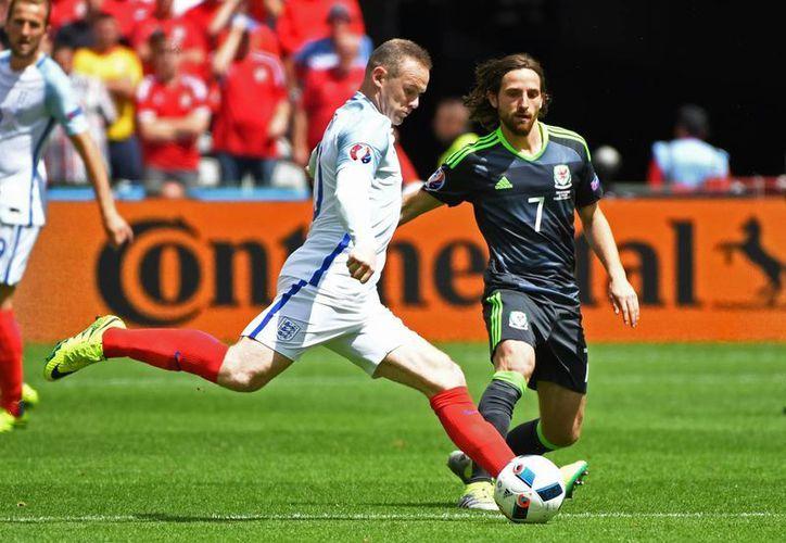 El inglés Wayne Rooney va por la pelota, a su lado el jugador de Gales Joe Allen, durante el partido de fútbol Euro 2016 Grupo B entre Inglaterra y Gales en el estadio Bollaert en Lens, Francia. (Foto AP/Geert Vanden Wijngaert)
