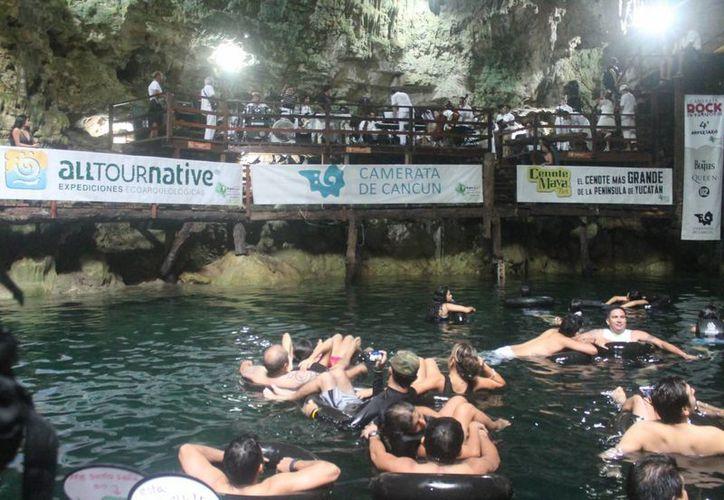 Los asistentes disfrutaron del conciertos sentados en salvavidas dentro del cenote. (Cortesía/Notimex)