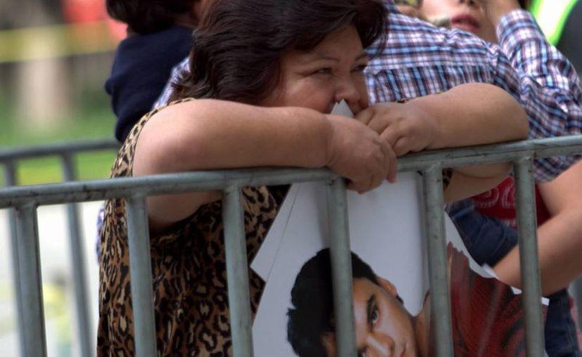 Las ventas de discos de Juan Gabril, quien falleció hace una semanas, se dispararon hasta casi 500 por ciento, según Universal Music. La imagen, de una fan en a las afueras del Palacio de Bellas, está utilizada solo con fines ilustrativos. (Notimex)