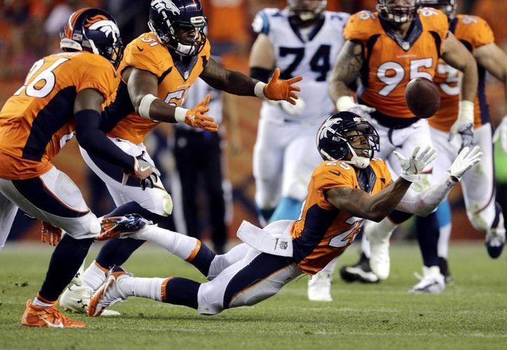 Chris Harris, de Broncos, al momento de interceptar un pase de Carolina. Al final, en el primer partido de temporada regular de la NFL, Broncos de Denver ganó 21-20. (AP)