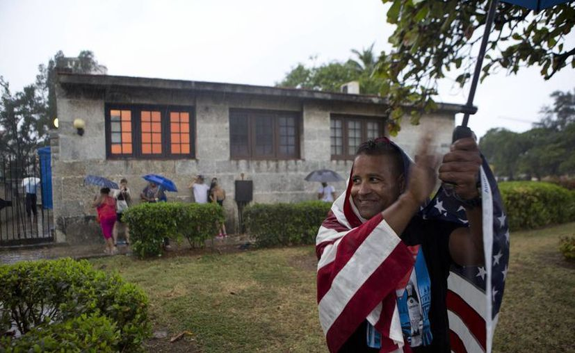 Un cubano con una bandera de EU sobre los hombros aplaude que el convoy del presidente Barack Obama, en La Habana Vieja, Cuba. (Archivo/Agencias)