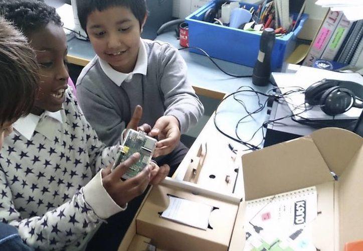 Unos niños revisan los componentes de Kano, una computadora de bajo costo, pensada para que los más pequeños aprendan informática. (EFE)