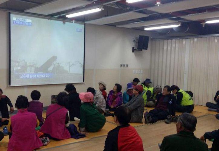 Vecinos de la isla Baengnyeong observan la televisión en un refugio este lunes. (EFE)