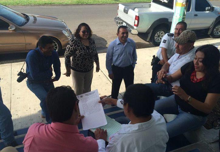Abogados, un par de ejidatarios y el actuario del Tribunal Agrario, Sergio Antonio Solís Arceo, en la entrada de la tienda. (Harold Alcocer/SIPSE)