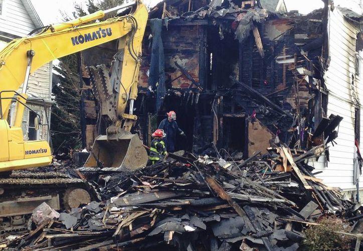 Los bomberos permanecen afuera de una casa que se quemó la madrugada del jueves 12 de enero del 2017 en Baltimore. Seis niños murieron en el incendio. (AP/Brian Witte)