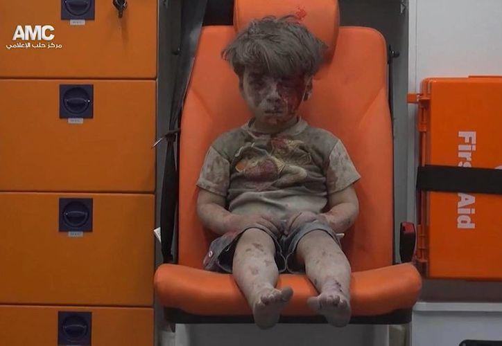En esta imagen, tomada de un video distribuido por el grupo opositor sirio Aleppo Media Center (AMC), aparece un niño sentado en una ambulancia tras ser rescatado de entre los escombros de un edificio alcanzado por un bombardeo aéreo en Alepo. (Aleppo Media Center via AP)