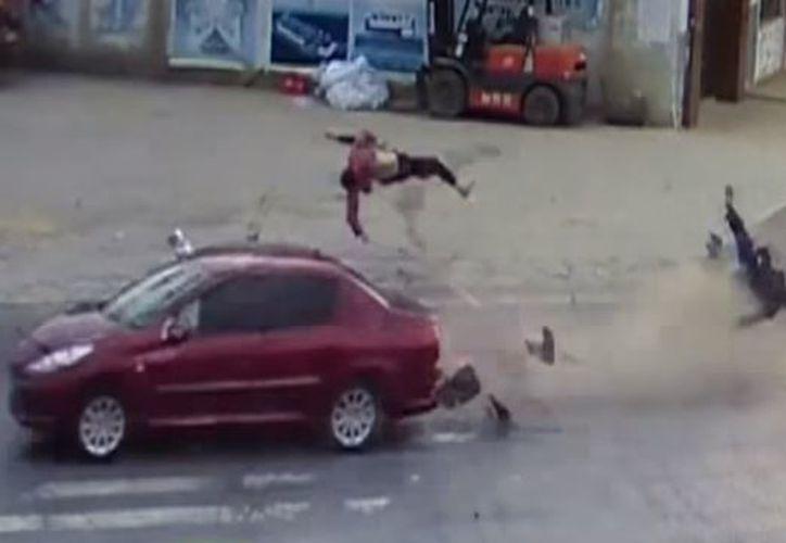 La pareja fue arrojada tras el impacto que recibió por parte de un automóvil. (Captura)