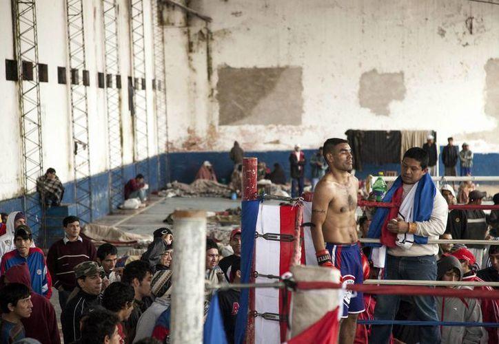 Un interno de la cárcel de Tacumbú, la mayor del país, ubicada en Asunción, Paraguay, descansa durante un combate en la exhibición de boxeo organizada en el patio de la prisión. (EFE)