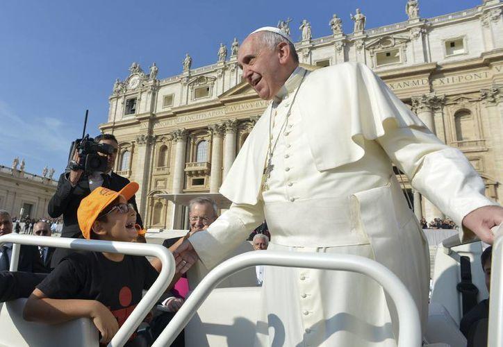 El Papa Francisco saluda a un niño al arribar en el papamóvil a la Plaza de San Pedro para su audiencia del miércoles 8 de octubre de 2014. (Foto: AP Photo/L'Osservatore Romano)