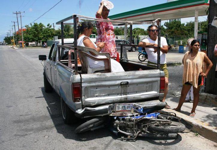 La motocicleta en la que permanecían estacionados dos jóvenes quedó prácticamente prensada entre las dos camionetas. (Irving Canul/SIPSE)