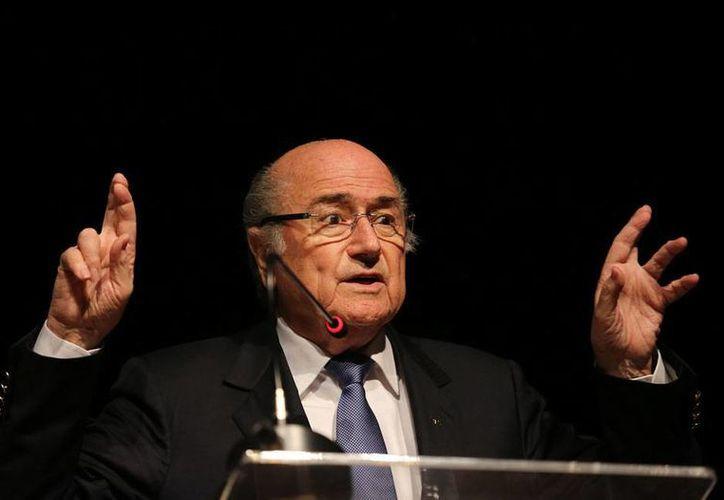 El presidente de FIFA, quien calificó como un éxito el Mundial de Brasil 2014, a pesar de que la justa no ha terminado, pidió 'cruzar los dedos' para que el campeonato termine bien. (AP)