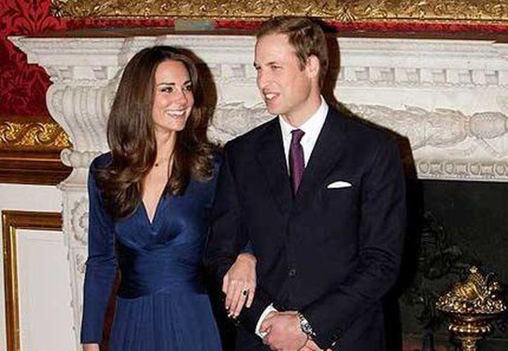 Kate Middleton con el vestido que utilizó el día que se comprometió con el príncipe Guillermo (junto a ella). (www.quieroirdecompras.com/Archivo)