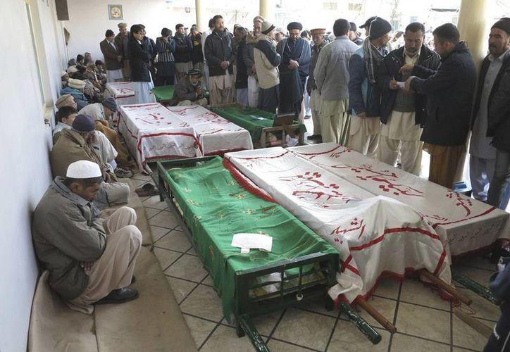 El grupo terrorista Lashkar-e-Jhangvi se atribuyó el atentado en el que murieron 22 personas, ayer en Pakistán. En la imagen, la gente rodea algunos de los cuerpos de los fallecidos. (Efe)