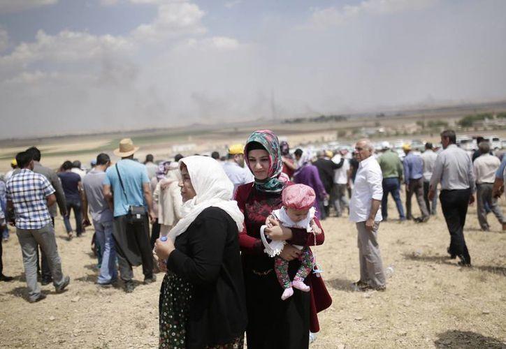 Una muchedumbre avanza de pie mientras se observa a lo lejos columnas de humo debidas a enfrentamientos entre integrantes del Estado Islámico y curdos en Kobani, Siria. (Foto: AP)