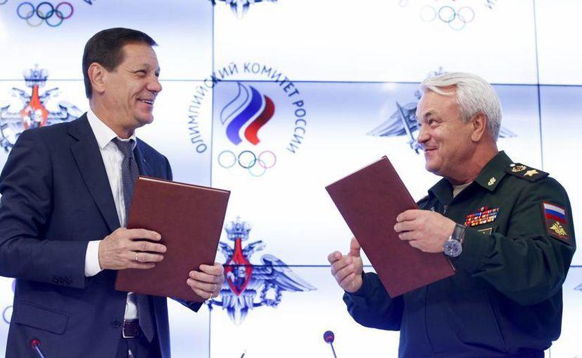 Alexander Zhukov (i), presidente del Comité Olímpico Ruso y el ministro de Defensa ruso, Nikolai Pankov, intercambian información alusiva a cooperación entre las partes, sobre todo para evitar el dopaje, lo cual ha dejado fuera de Río 2016 a más de 80 rusos hasta ahora. (AP)