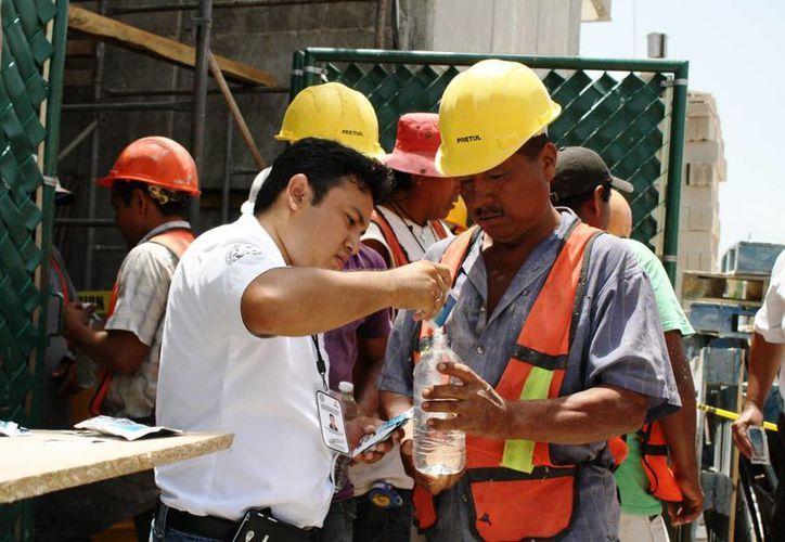 Protección Civil repartió agua y suero entre los trabajadores de la construcción ayer. (Octavio Martínez/SIPSE)