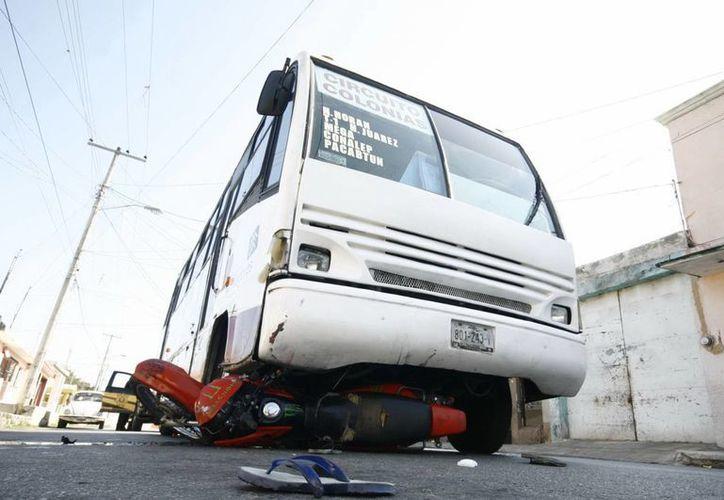 La motocicleta derrapó y quedó debajo del autobús. (Jorge Sosa/SIPSE)