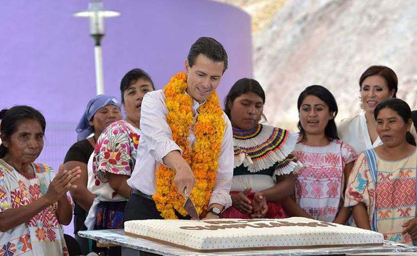 En su visita a Tlapa de Comonfort, Guerrero, Peña Nieto aprovechó para cortar pastel para celebrar su 49 cumpleaños. (Presidencia)