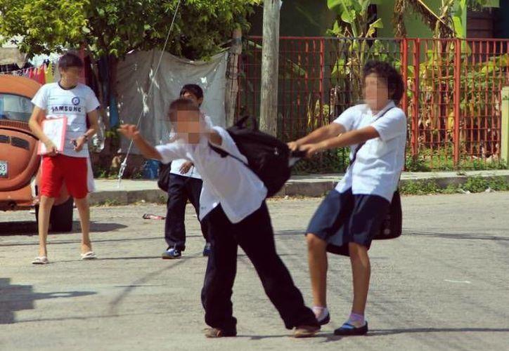 Una niña llevó un arma blanca a la escuela y amenazó a un compañero con hacerle daño. Dos menores juegan en las afueras de una escuela. (Imagen de contexto de archivo/SIPSE)