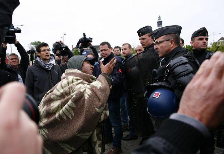 Un inmigrante afgano discute con los oficiales de la policía francesa después de que comenzaron a desmantelar su campamento. (Agencias)
